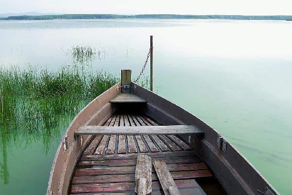 Ein Ruderboot aus Holz an einem stillen See. Das Bild wirkt sehr entspannend, so wie die Focusing Kurse und Seminare von Monika Timme.
