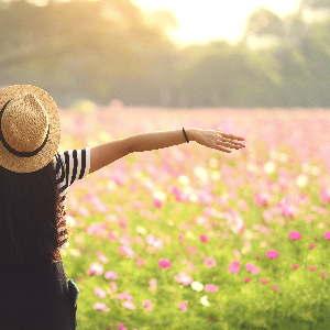 Frau mit Strohhut vor einer Blumenwiese. So freut man sich über eine Focusing Ausbildung.