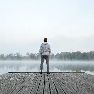 Ein Mann steht auf einem Holzsteg an einem See im Morgendunst. Coaching Focusing mit Monika Timme