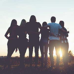 Eine Gruppe von jungen Menschen vor einem Sonnenuntergang als Symbol für Focusing Seminare mit Monika Tiimme.