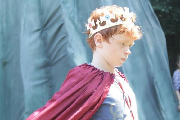 Ein Junge mit Krone und Königsumhang spielt einen König in der Theatertherapie.