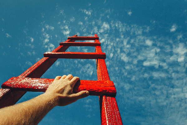 Eine rote Leiter ragt in den Himmel und man sieht auf der ersten Sprosse eine Hand. Coaching in Bonn mit Monika Timme.