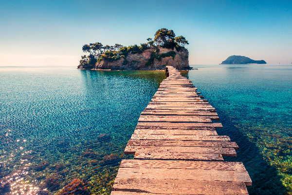 Ein Holzsteg führt auf eine kleine Insel im blauen Meer. Coaching Focusing mit Monika Timme.