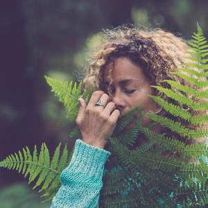 Eine Frau in einem blauen Pullover genießt den Geruch von frischen Farn im Wald. Ein frischer Geruch wie eine focusingtherapie mit Monika Timme