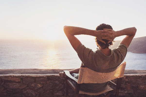 Ein Mann entspannt in einem bequemen Stuhl mit Blick auf einen See. Focusingtherapie für innere Gelassenheit und Ausgeglichenheit.