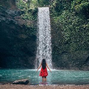 Eine Frau in einem roten Kleid vor einem Wasserfall. Es symbolisiert die Kraftquellen im Focusing